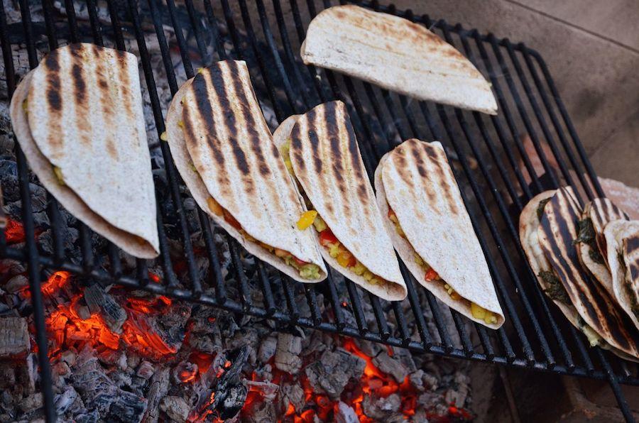 Vegane Quesadillas mit Melone, Avocado und Mango über glühenden Kohlen.